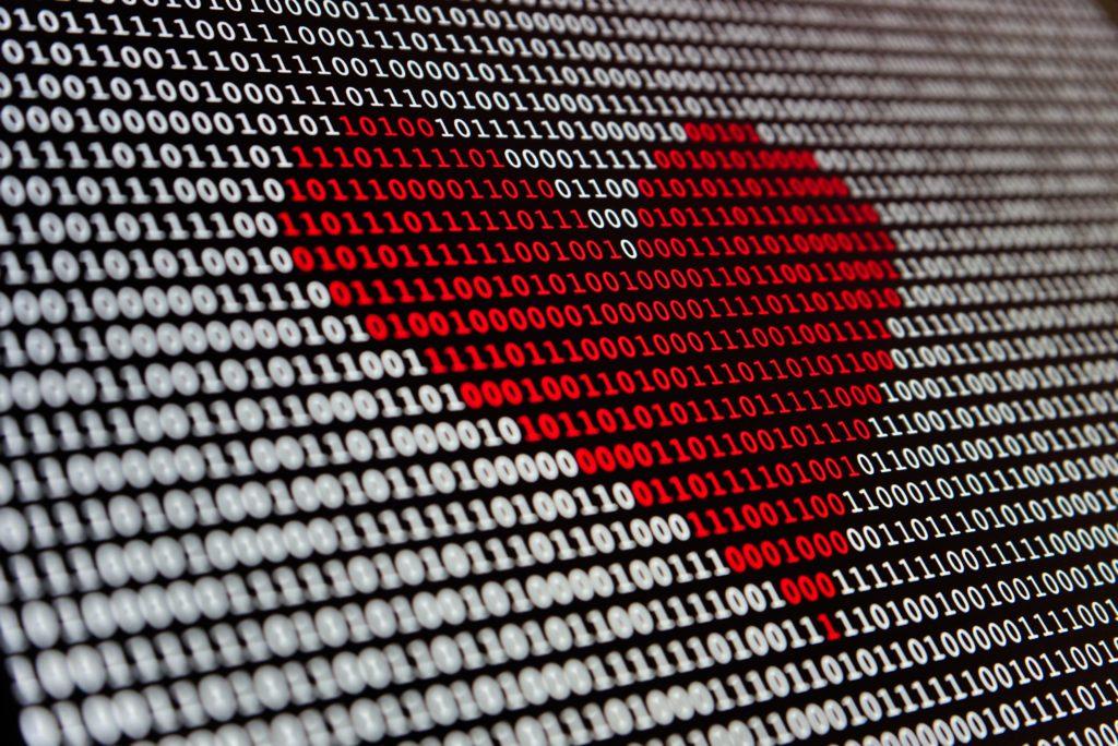 image highlighting red heart in white binary code
